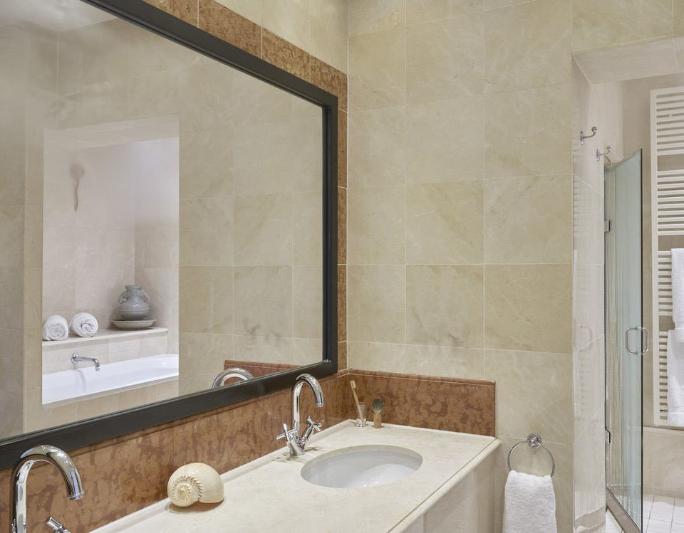 bathroom sink property mirror tile plumbing fixture flooring home bathtub tan