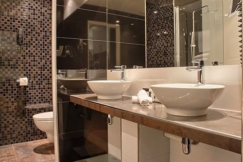 bathroom sink mirror property plumbing fixture bathtub flooring tile vessel tiled