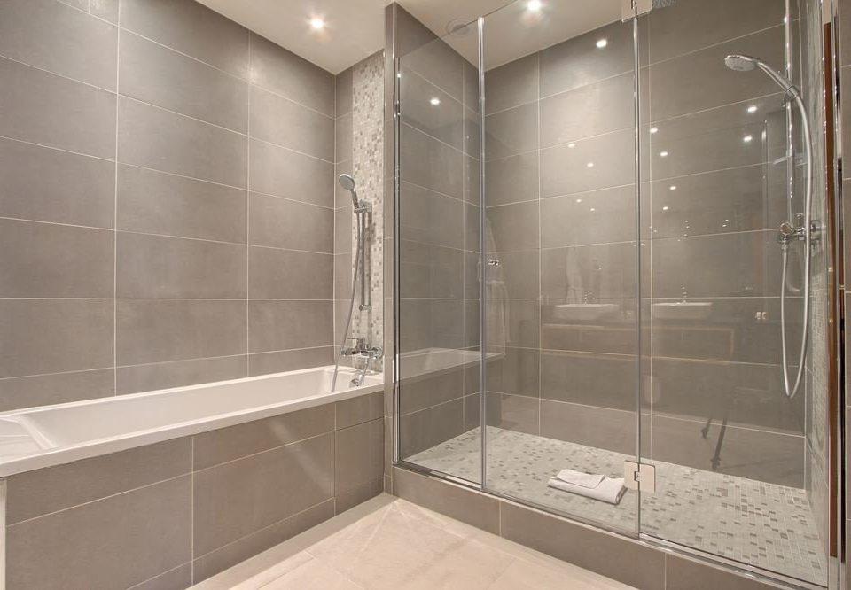 bathroom shower scene plumbing fixture tile flooring stall bathtub tiled