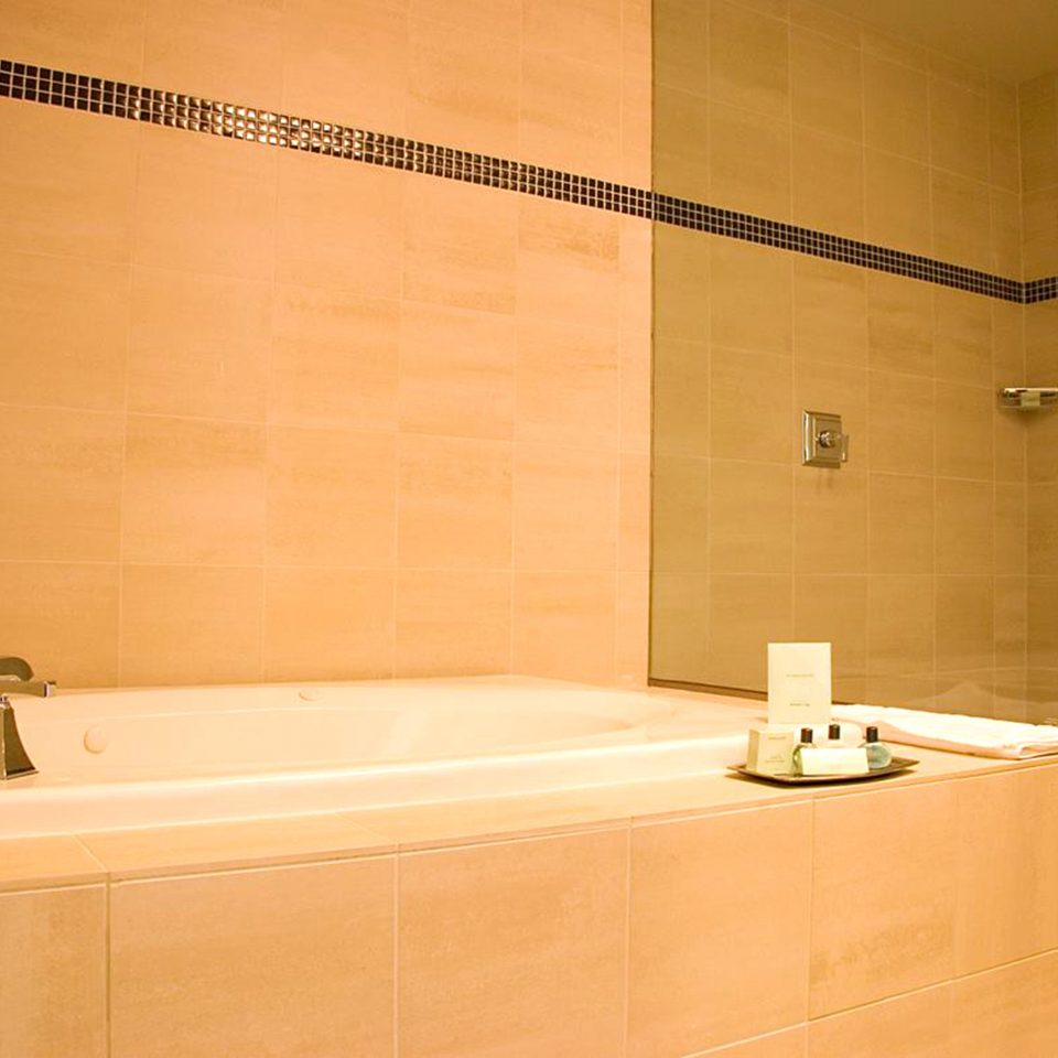 bathroom bathtub plumbing fixture tile flooring sink tan