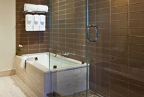 bathroom plumbing fixture bathtub flooring tile tiled tub tan