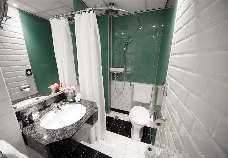 bathroom toilet property green sink plumbing fixture public toilet white bathtub tiled tile