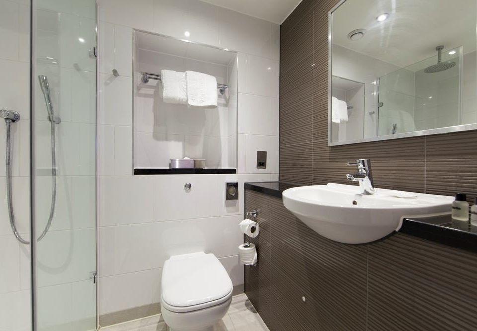 bathroom mirror sink property toilet bidet white plumbing fixture flooring towel rack tile