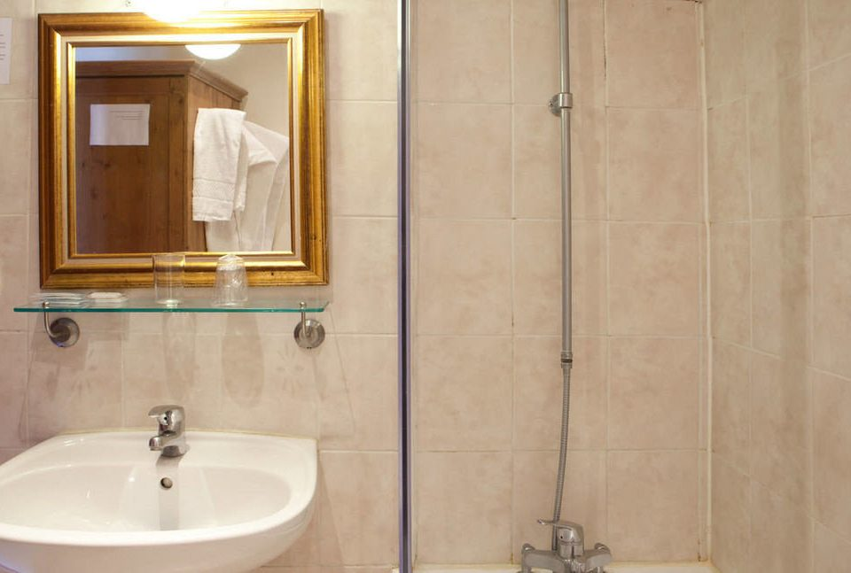 bathroom sink plumbing fixture flooring white tile toilet bidet tiled tan