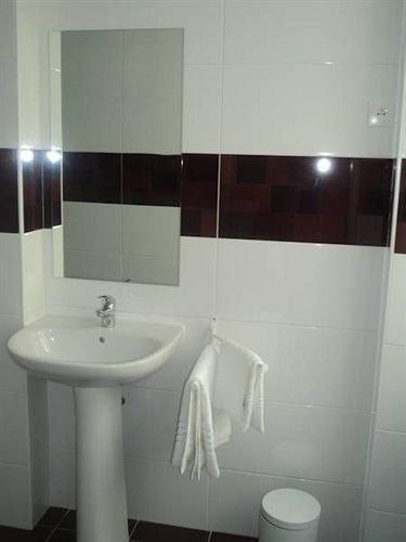 bathroom property sink white toilet plumbing fixture bidet flooring tile tiled