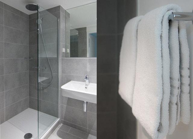 bathroom towel white plumbing fixture shower sink bidet flooring toilet rack tiled
