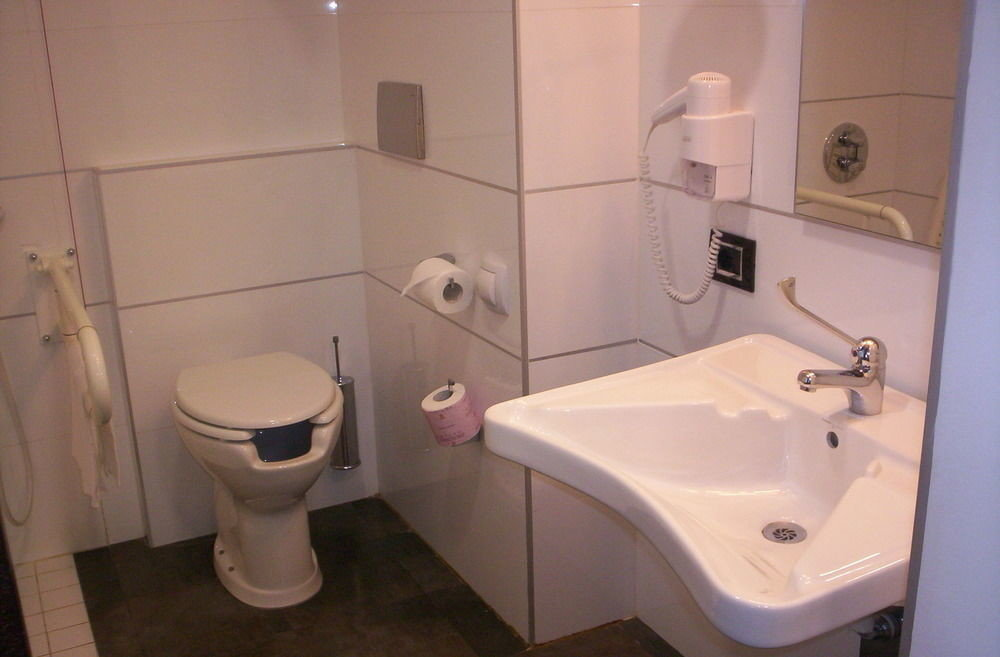 bathroom toilet property sink plumbing fixture bidet public toilet tile trash tiled