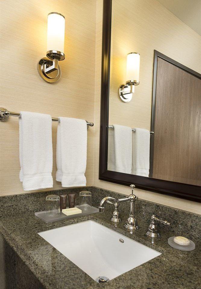bathroom sink mirror towel countertop vanity toilet double counter plumbing fixture lighting flooring clean rack tan