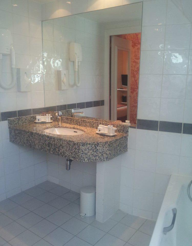 bathroom property toilet countertop plumbing fixture tile flooring sink material tiled
