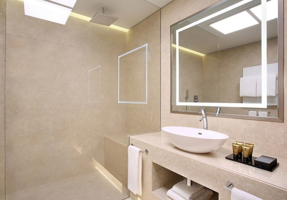 bathroom sink mirror property plumbing fixture flooring home tile public toilet tan