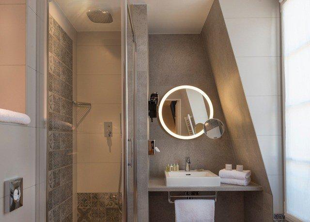 bathroom property toilet home plumbing fixture sink flooring tile tan tiled