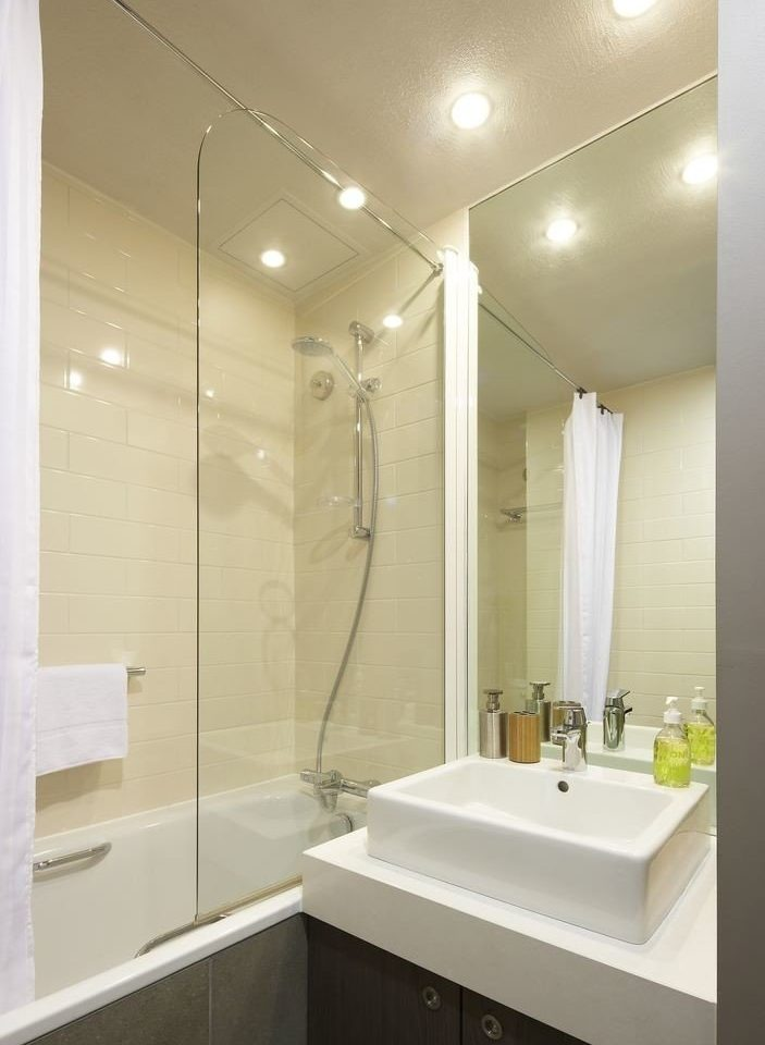 bathroom mirror sink lighting white plumbing fixture flooring tan