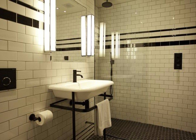 bathroom toilet flooring tile lighting tiled sink plumbing fixture public toilet public