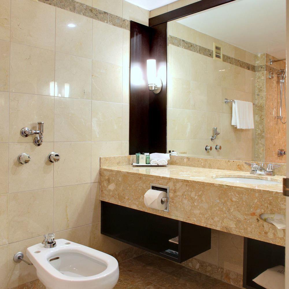 bathroom toilet sink mirror property plumbing fixture flooring tile tan tiled