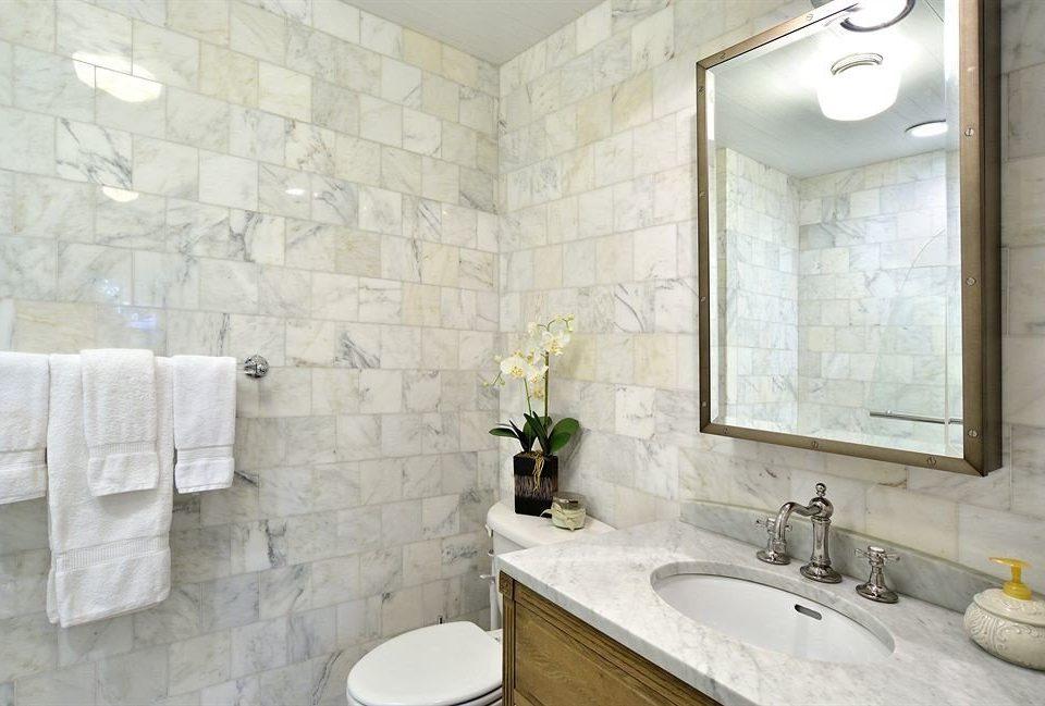 bathroom sink property flooring tile toilet white tan tiled