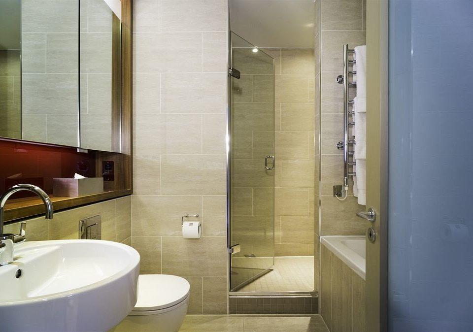 bathroom mirror sink property plumbing fixture toilet public toilet tile tan tiled