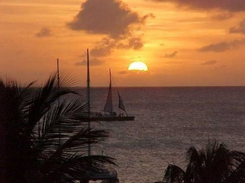 Beach Beachfront Boat Sunset sky water Sun horizon sunrise Sea afterglow dawn Ocean morning evening Coast dusk sailing vessel setting shore clouds distance day