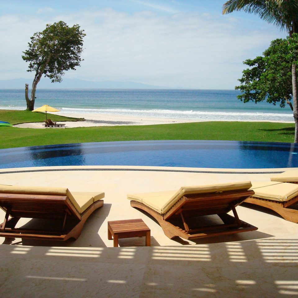 Beachfront Grounds Luxury Pool tree sky water leisure swimming pool Resort Beach Sea Villa lined shore Deck line Boat