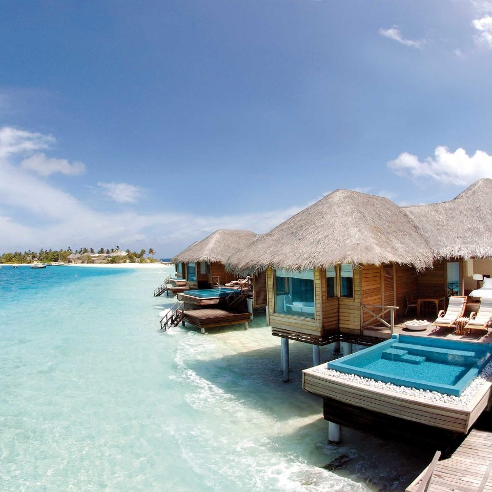 Beach Beachfront Elegant Luxury Overwater Bungalow Romantic Scenic views Waterfront sky water Boat property Resort caribbean Sea swimming pool Nature blue Lagoon shore