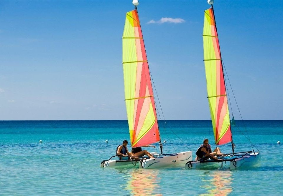 Beach Beachfront Luxury Ocean Tropical water sky Boat sailboat dinghy sailing sail watercraft vehicle transport sailing sailing ship sports windsurfing catamaran ship keelboat wind sailboat racing mast yacht racing dinghy proa sailing vessel