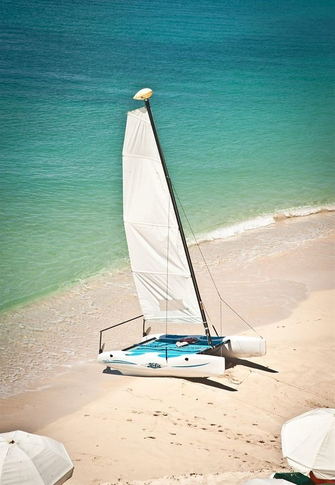 Beach Beachfront Boat Ocean Outdoor Activities Romantic water sailboat sail blue Sea vehicle Nature watercraft dinghy sailing surfing equipment and supplies sand shore surfboard wind sandy sailing vessel