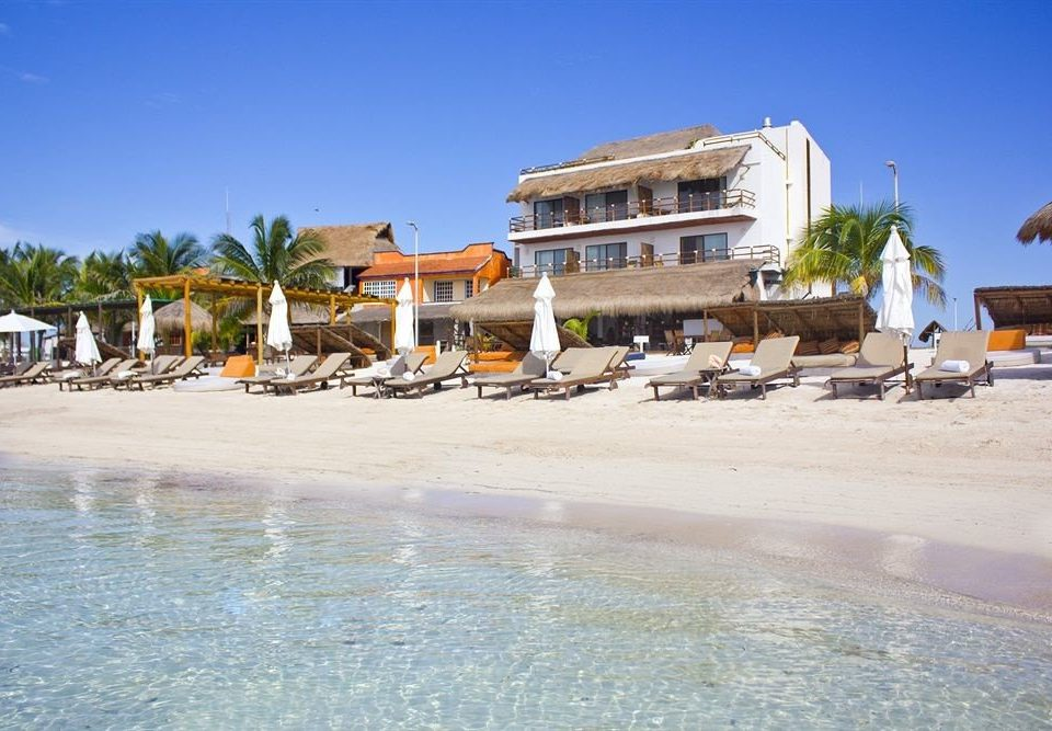 Beachfront Buildings Exterior Grounds Ocean Rustic Tropical sky Beach Sea shore Resort Coast marina dock