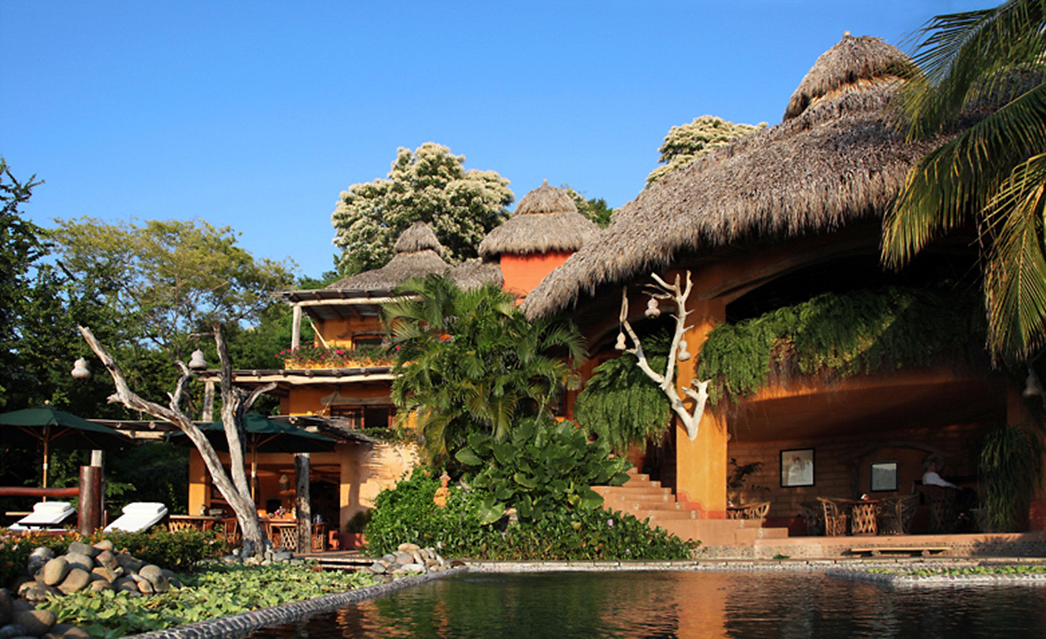 Beach Beachfront Buildings Exterior Mountains Ocean tree sky plant Resort house Village home Jungle Villa Garden