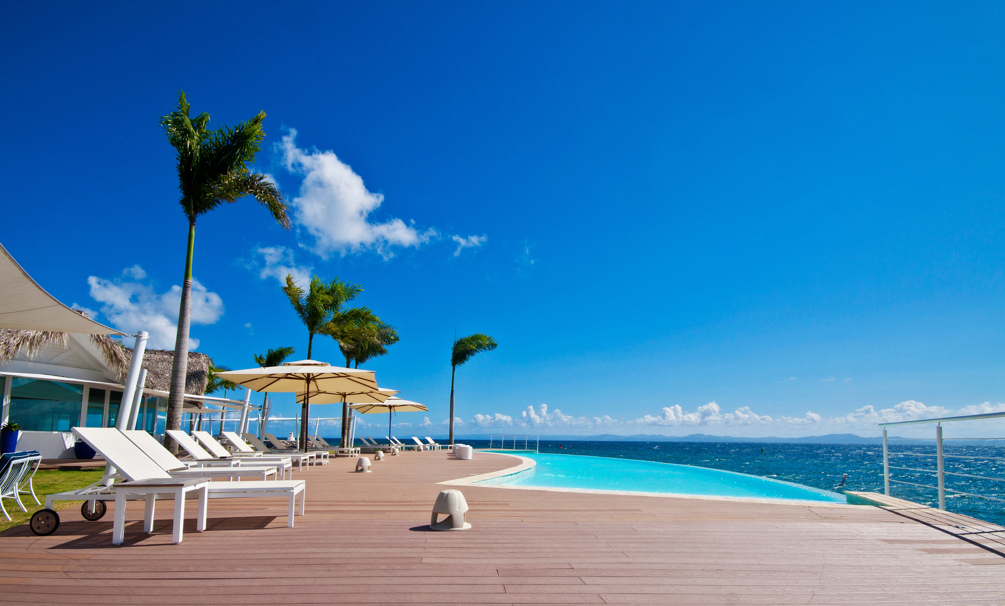 Beachfront Lounge Luxury Pool Scenic views sky ground umbrella chair Beach caribbean swimming pool Sea Ocean Resort Nature shore blue Coast Lagoon marina dock Deck sandy day