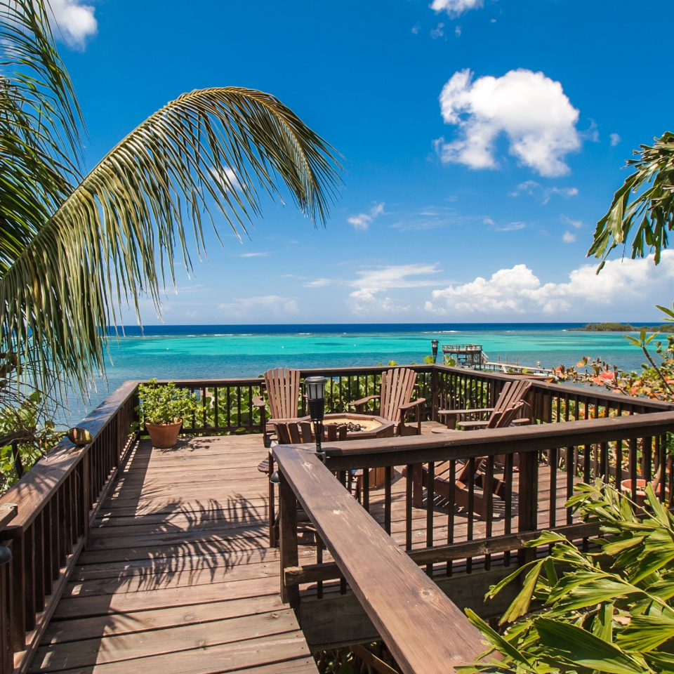Beachfront Deck Fireplace Island Jungle Patio Romance Scenic views Waterfront tree sky bench palm Beach leisure caribbean park Resort walkway tropics Ocean plant arecales Sea Coast palm family boardwalk lined shade overlooking sandy