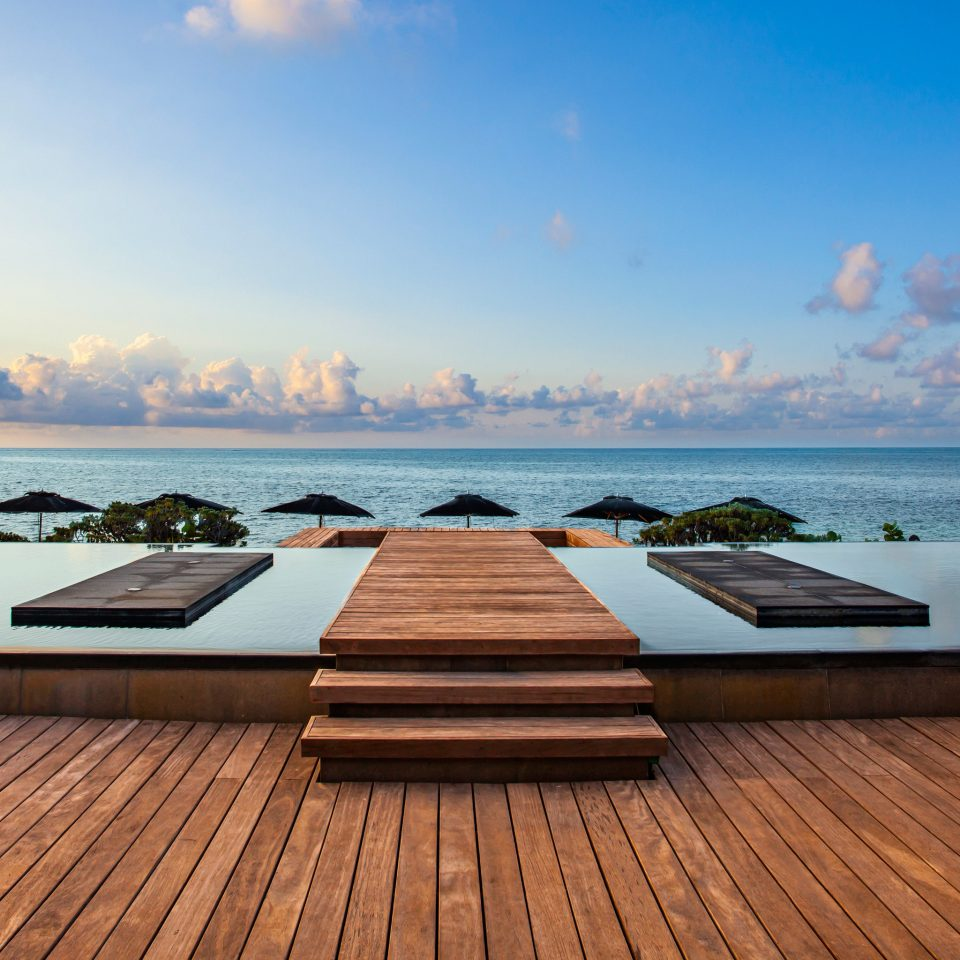 Beachfront Hotels Luxury News Pool Romance Trip Ideas Waterfront sky water Sea horizon wooden Ocean shore morning Sunset Beach swimming pool Coast dusk Deck overlooking
