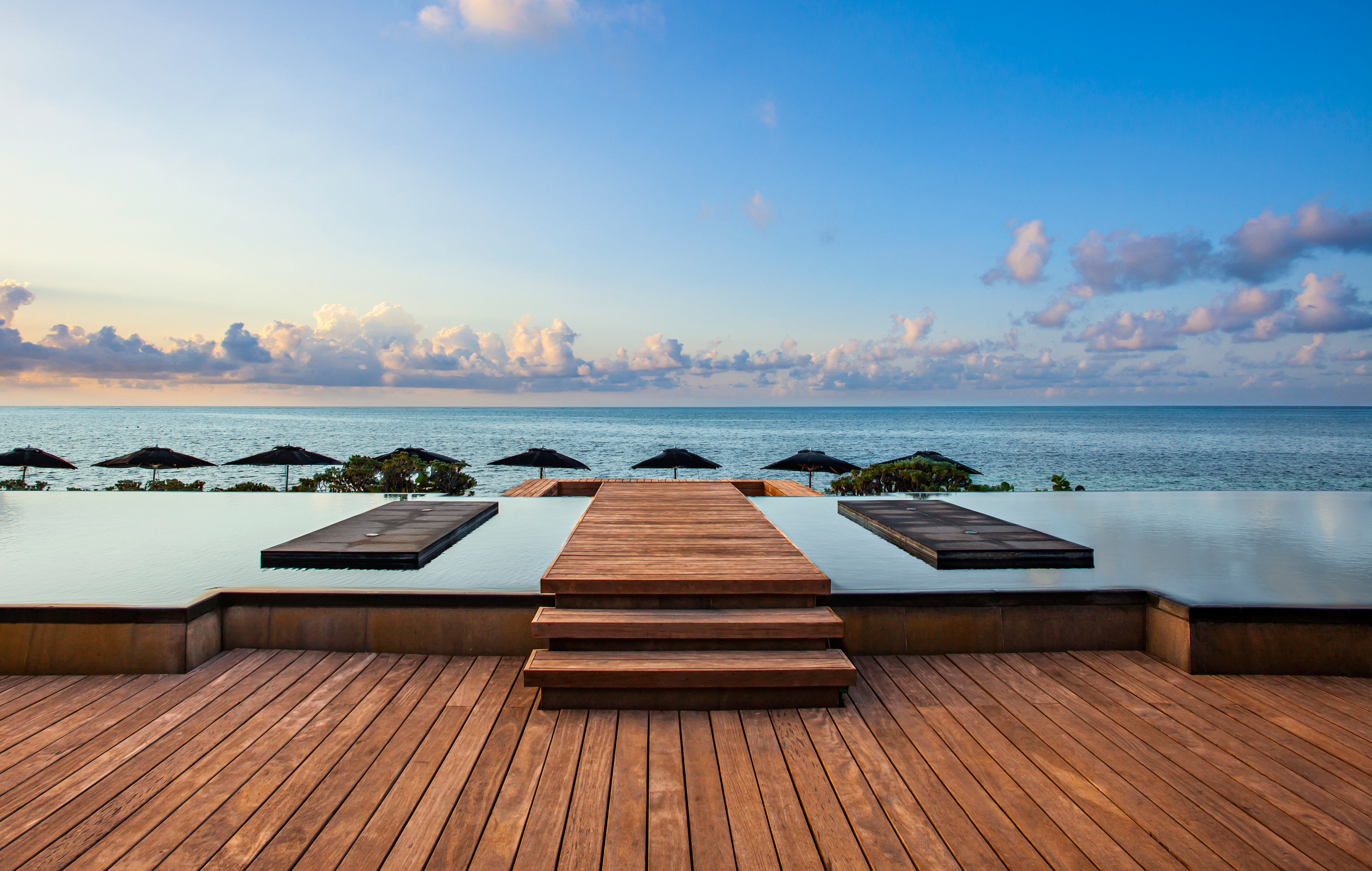 Beachfront Hotels Luxury News Pool Romance Trip Ideas Waterfront sky water Sea horizon wooden Ocean shore morning Sunset Beach swimming pool Coast dusk Deck overlooking