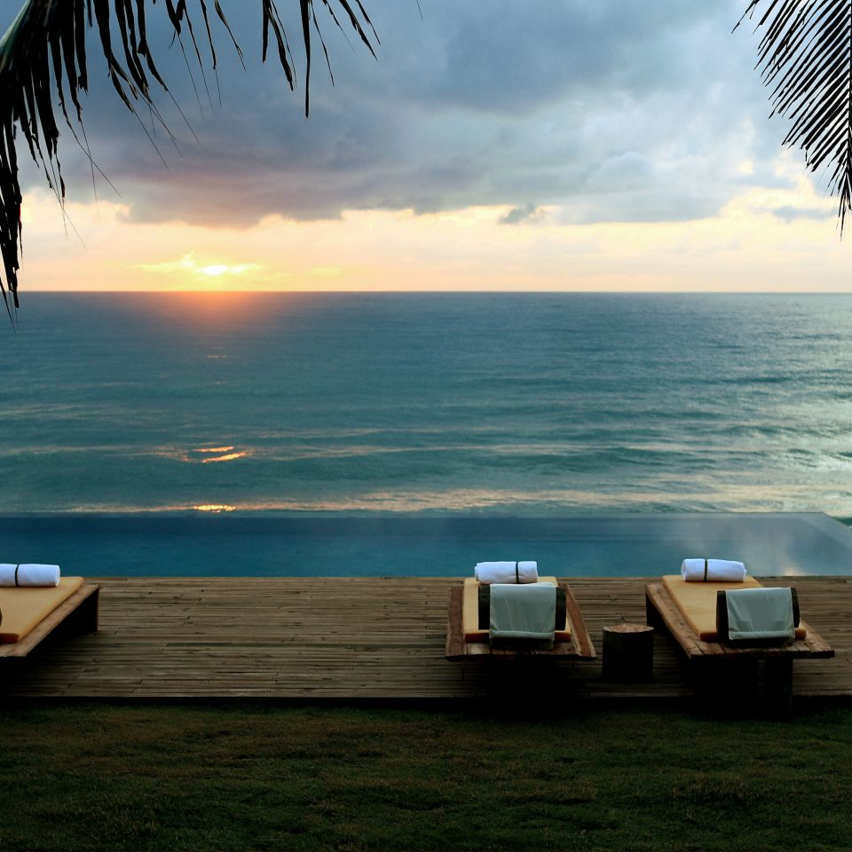 Beach Beachfront Deck Eco Modern Ocean Patio Pool Romantic Scenic views Sunset Waterfront sky water Sea shore horizon Coast morning caribbean arecales sunlight tree evening palm overlooking wave tropics dusk sandy