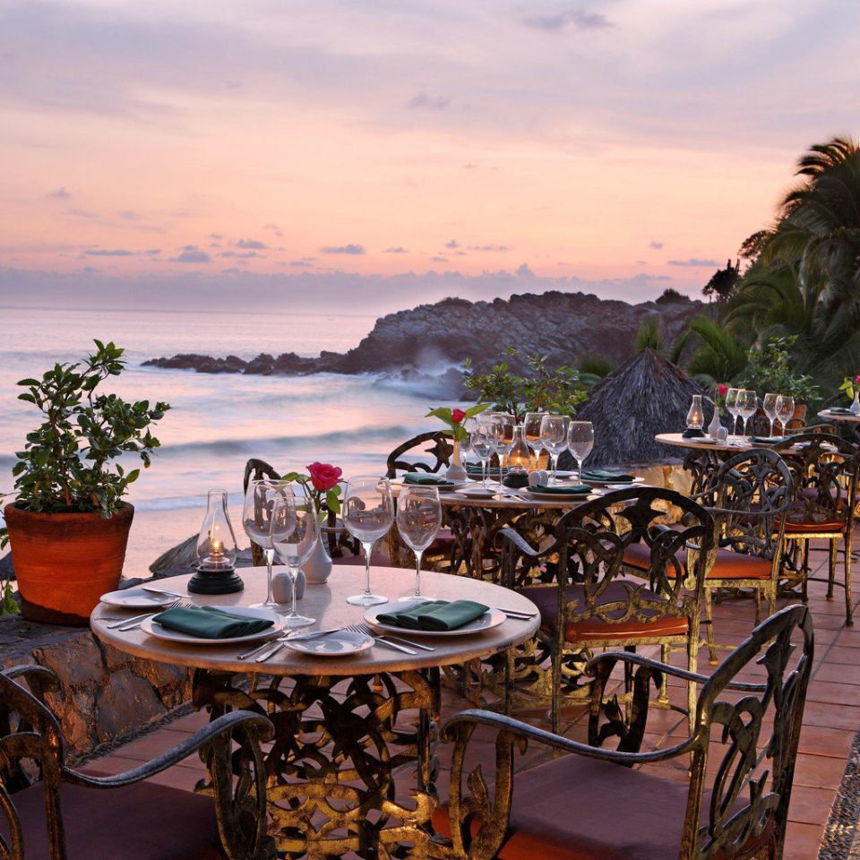 Beachfront Dining Drink Eat Sunset Tropical Waterfront sky Beach Sea Resort Coast Ocean set shore