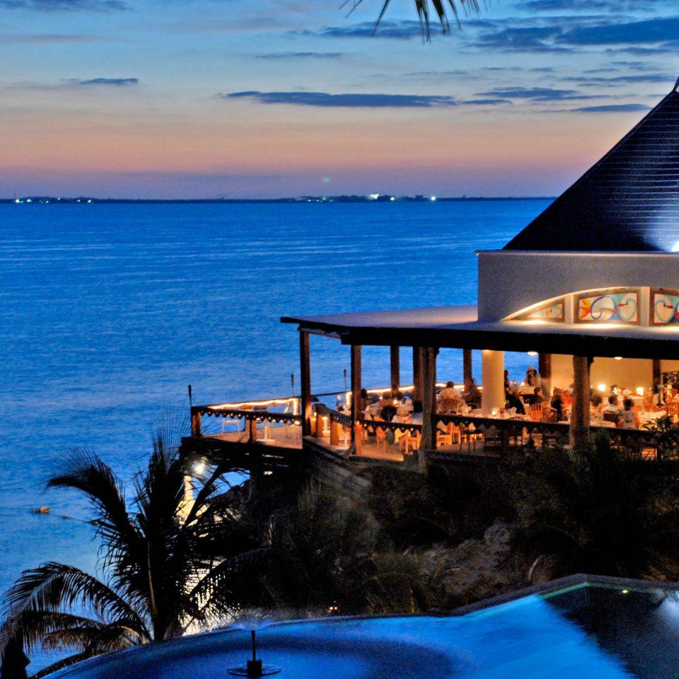 Beachfront Dining Drink Eat Luxury Ocean Pool Sunset Waterfront water sky Sea blue Beach Coast shore evening dusk Resort wave cape