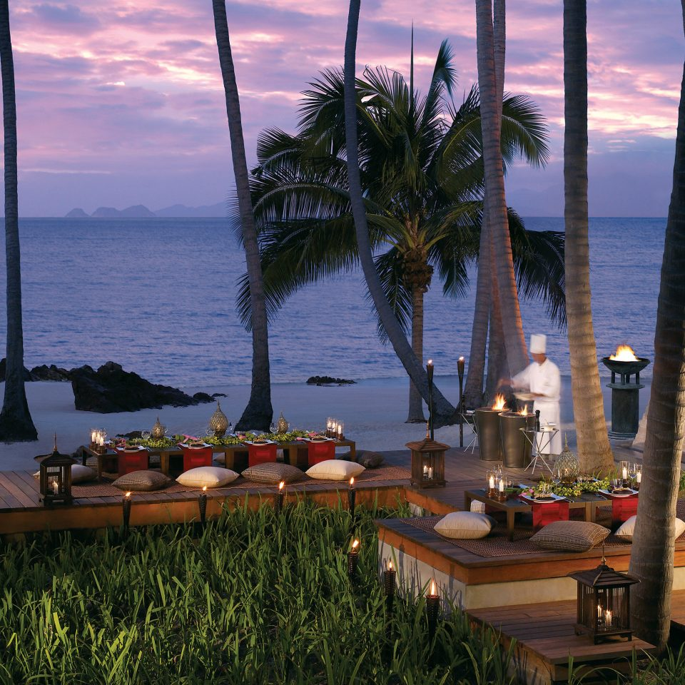 Beachfront Dining Drink Eat Honeymoon Jungle Outdoors Romance Romantic Sunset Tropical Waterfront sky water plant arecales Ocean Sea Coast Resort evening tree palm overlooking Lake Beach tropics