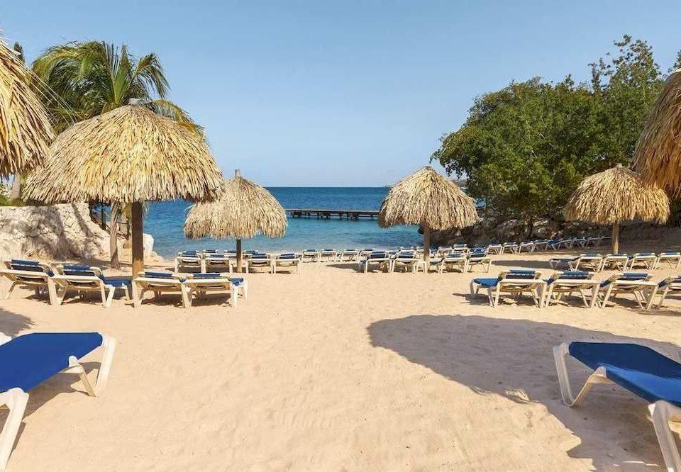 Beach Beachfront Exterior Ocean Romantic Tropical ground sky umbrella chair leisure property Resort sand lawn sandy laying Sea Coast swimming pool Villa caribbean lined shade shore day