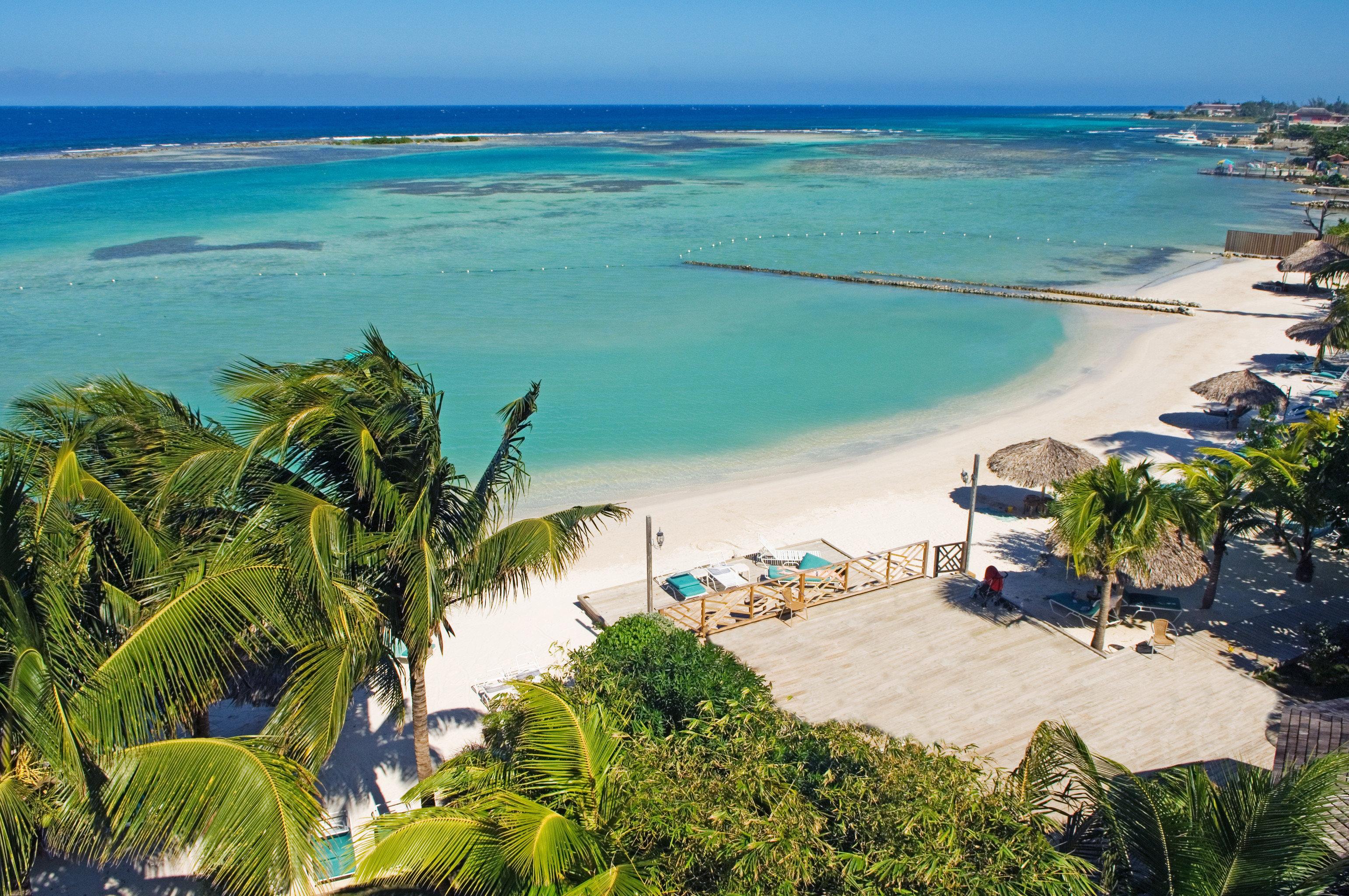 Beach Beachfront Grounds Island water sky Nature Sea Coast caribbean Ocean tropics Resort reef shore cape Lagoon arecales cove islet overlooking lined palm plant