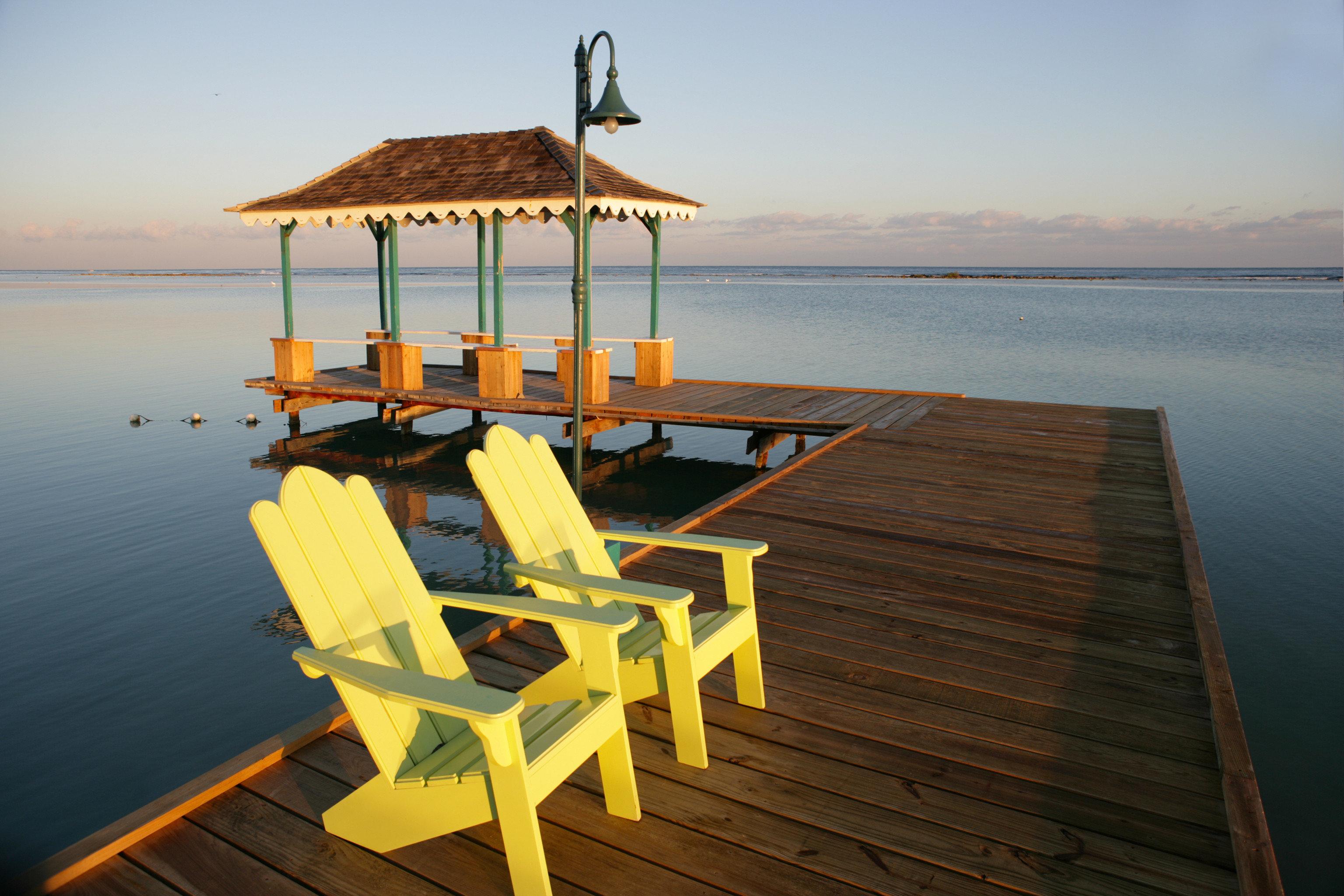 Beachfront Grounds Island sky water Beach chair Sea pier wooden Ocean dock shore Coast walkway Resort vehicle boardwalk overlooking