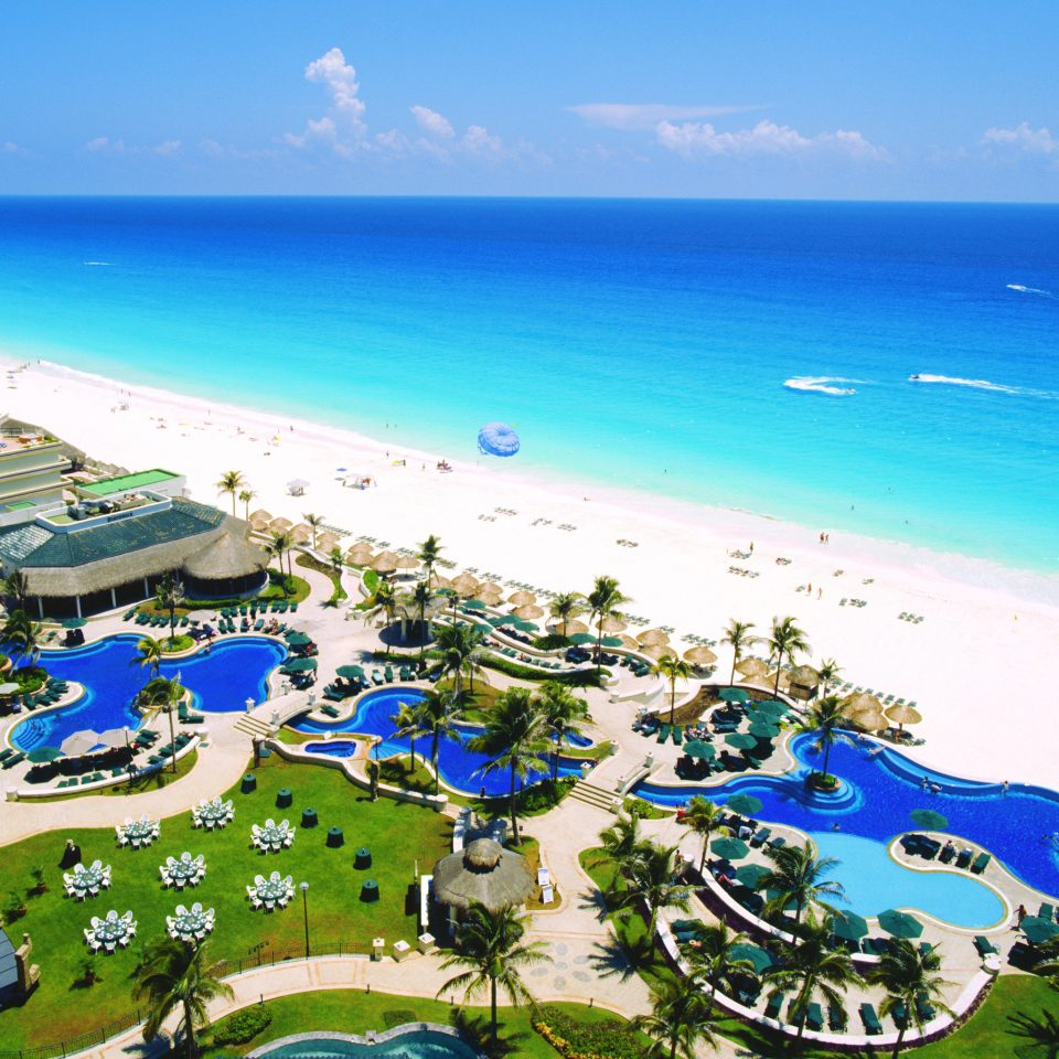 Beach Beachfront Grounds Pool Resort sky water umbrella leisure caribbean Ocean Coast Sea cape lawn blue day shore