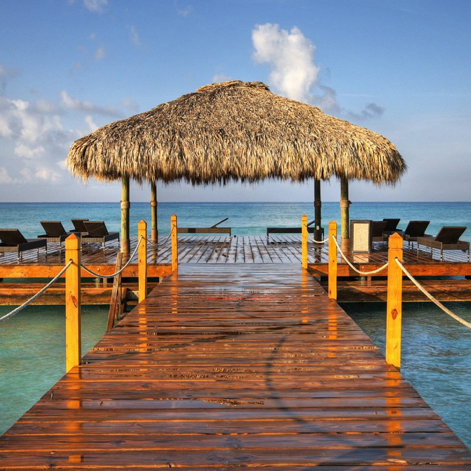 Beach Beachfront Lounge Luxury Ocean water sky umbrella chair Sea leisure shore scene pier Coast Resort caribbean Lagoon travel Island Harbor orange