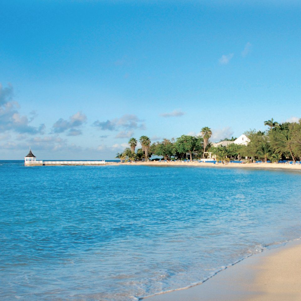 Beach Beachfront Island Waterfront water sky Sea shore Nature Ocean horizon caribbean Coast Lagoon tropics cape islet sand blue wave day sandy
