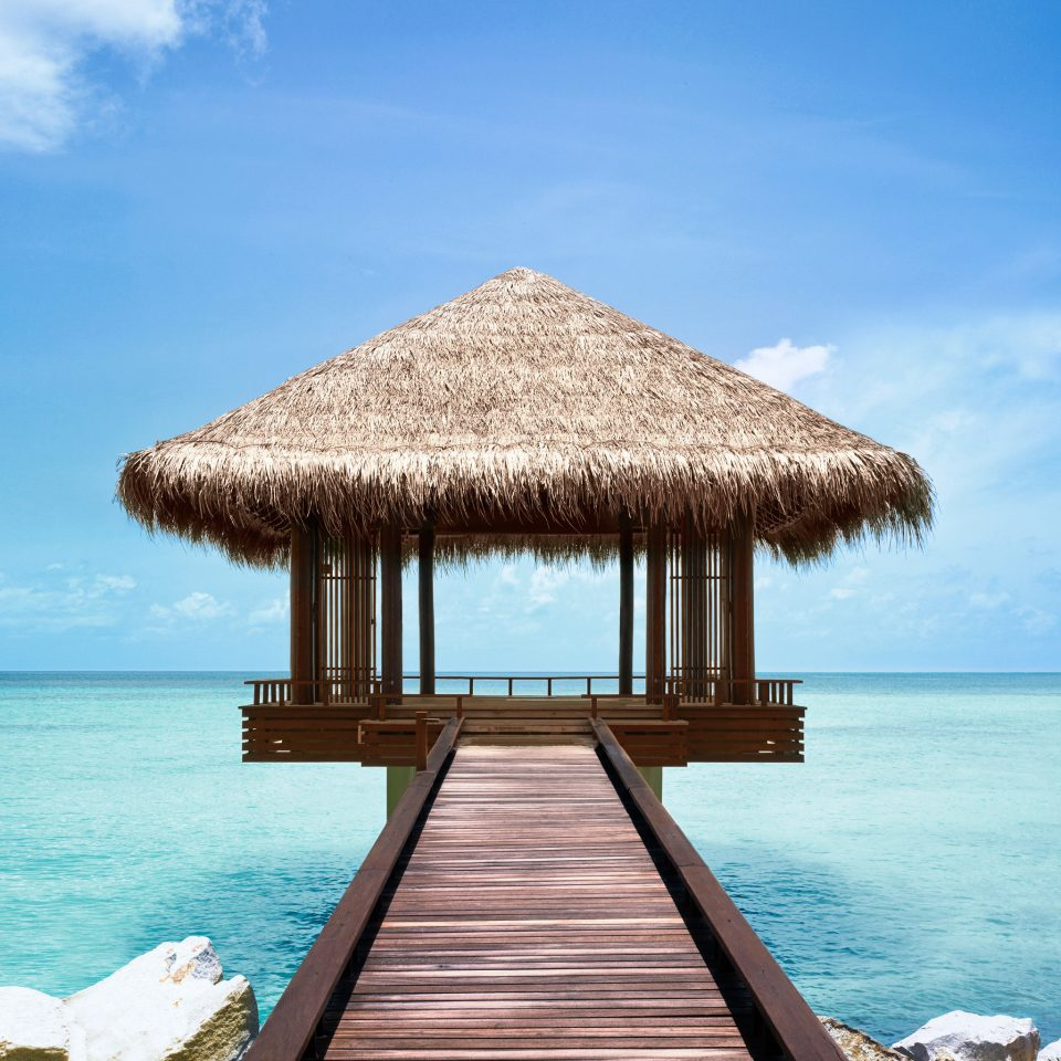 Beach Beachfront Luxury Romance Romantic Tropical Wellness water sky Sea Ocean Coast shore wooden caribbean Resort hut Island Lagoon cape sand overlooking swimming day