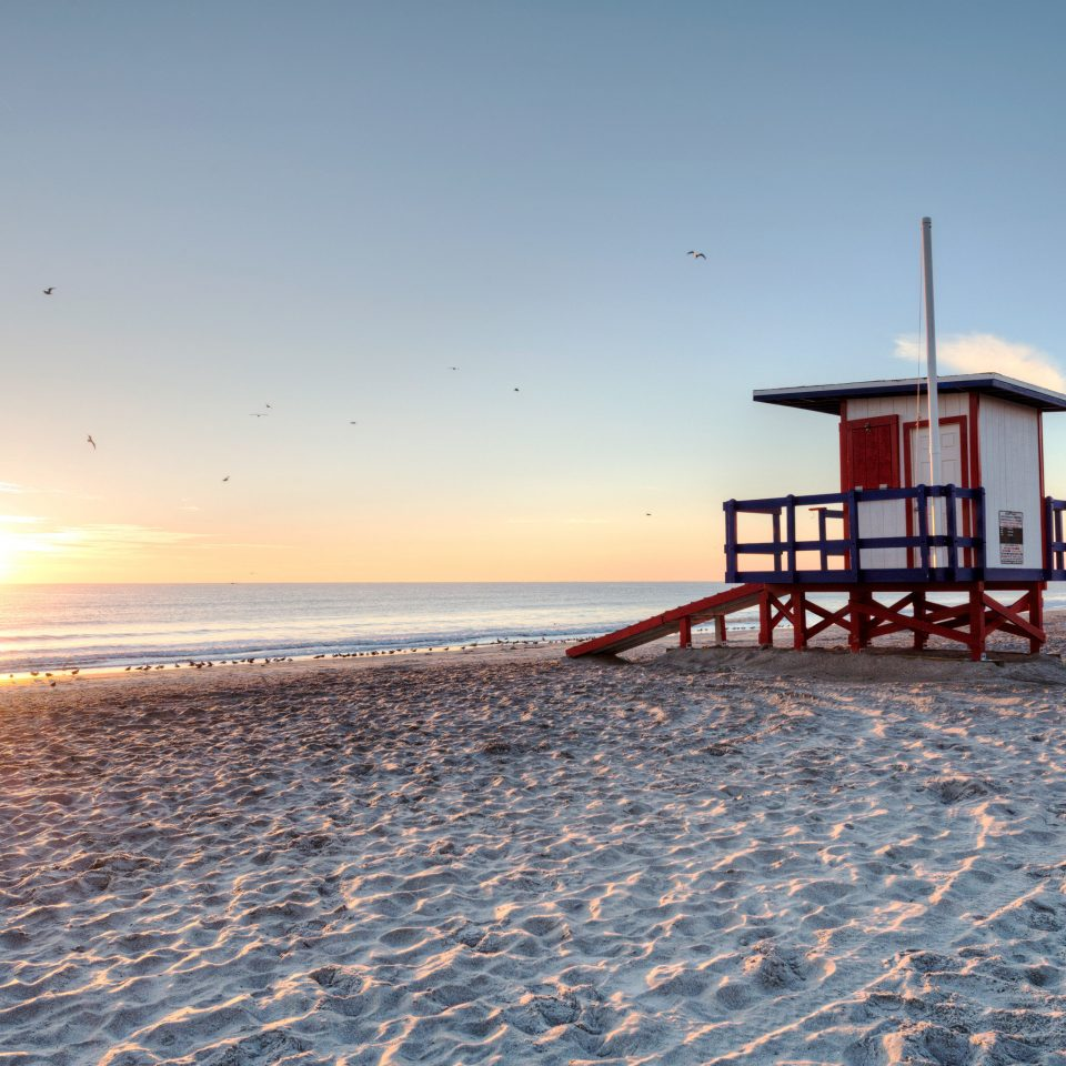 Beach Beachfront Ocean Sunset sky water ground Sea shore Coast horizon pier tower morning sunrise evening sand wave dusk walkway boardwalk lighthouse sandy