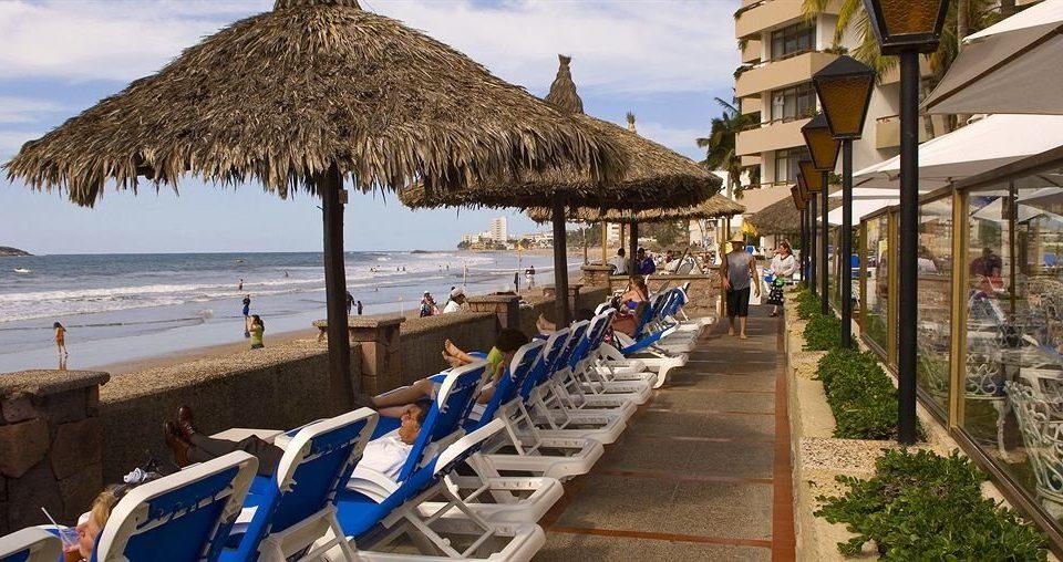 Beachfront Resort umbrella chair Beach walkway Town boardwalk lawn Coast Sea Village travel lined shade sandy line