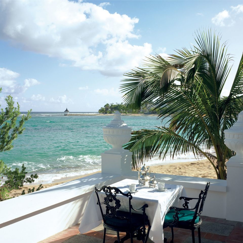 Beachfront Dining Island Patio Waterfront sky tree water Beach ground property caribbean Sea Ocean arecales palm Resort Villa home shore tropics swimming pool condominium Deck plant sandy shade day