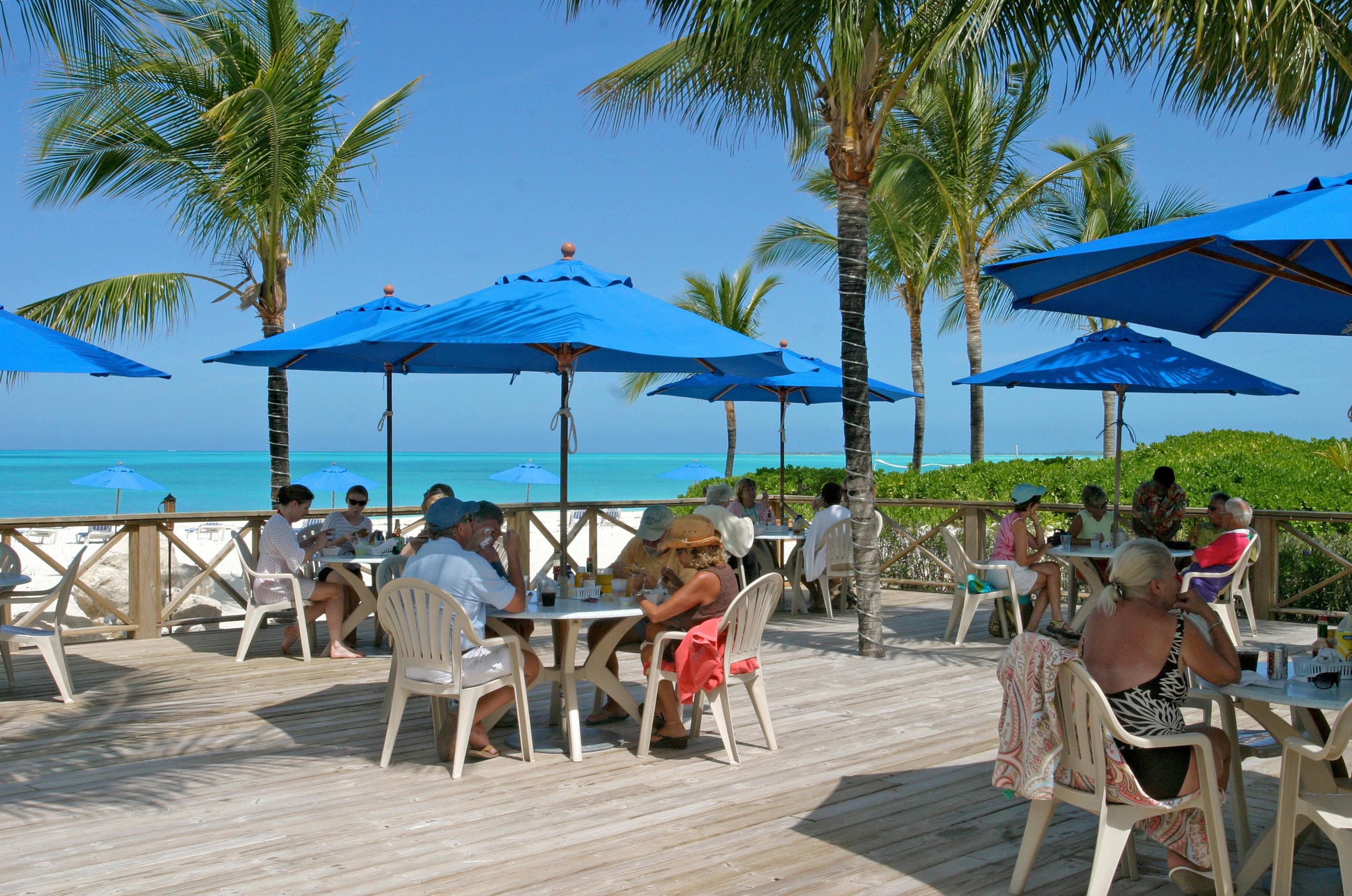 Beachfront Dining Drink Eat Grounds Resort tree sky umbrella chair ground leisure palm Beach caribbean walkway boardwalk Deck shade set shore
