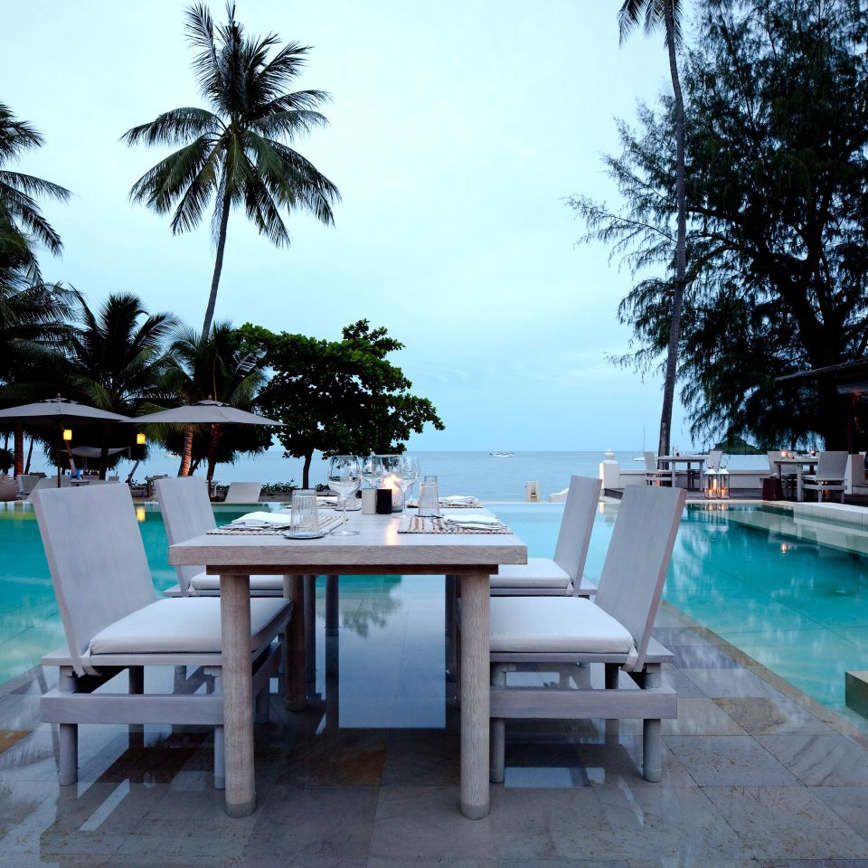 Beachfront Dining Drink Eat Outdoors Patio Pool Scenic views Tropical Waterfront tree sky leisure swimming pool property chair Resort caribbean dock home Villa Beach restaurant marina Sea condominium palm Deck shore sandy