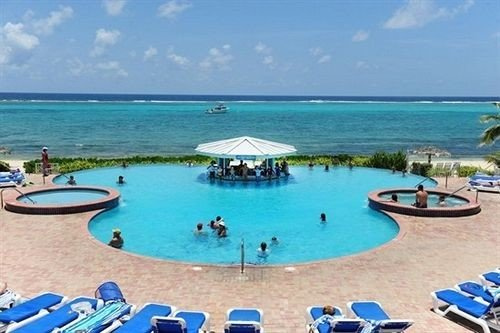 Beach Beachfront Lounge Pool water sky ground chair umbrella Ocean swimming pool Nature property Resort leisure caribbean shore resort town lawn Lagoon Villa lined reef blue enjoying day Deck sandy swimming