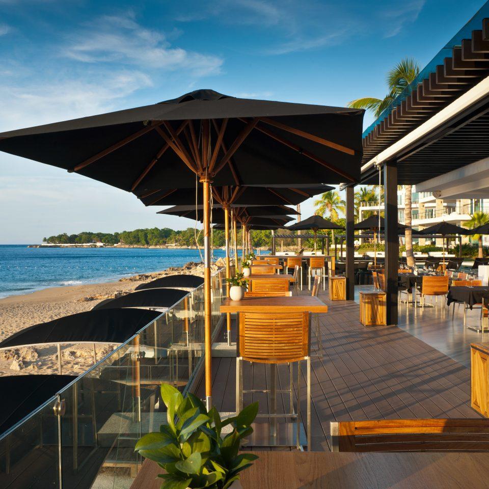 Beachfront Dining Eat Luxury sky chair umbrella water Resort restaurant Beach walkway shore empty