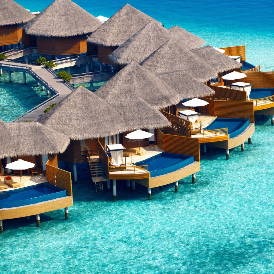 Beachfront Elegant Hotels Lounge Luxury Ocean Overwater Bungalow water chair umbrella leisure blue Sea swimming pool Resort Beach caribbean vehicle dock Harbor marina Water park Island swimming